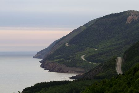 View of winding coastal road of Cape Breton National Park in Nova Scotia, Canada with twisting highwa, open ocean, green mountains, and pink streaked sky