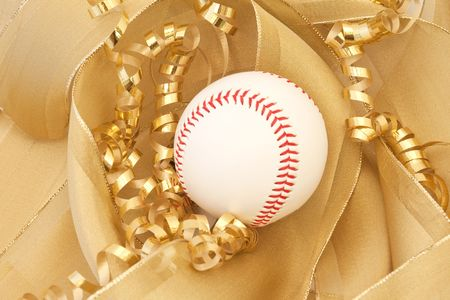 White baseball with sharp red stitching against a background of two types of intertwining, gold ribbons show the beloved game as a gift