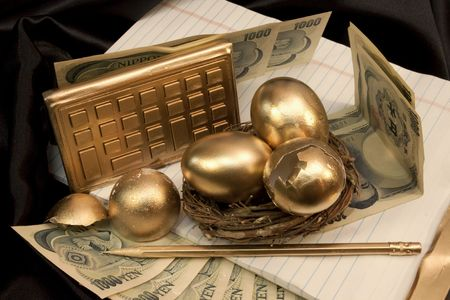 Nest Eggs, broken and whole, with gold calculator and gold pencil, are shown against a black satin background with yen currency and white legal pad