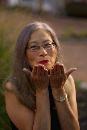 Asian woman with long, gray hair raises her hands to blow kisses