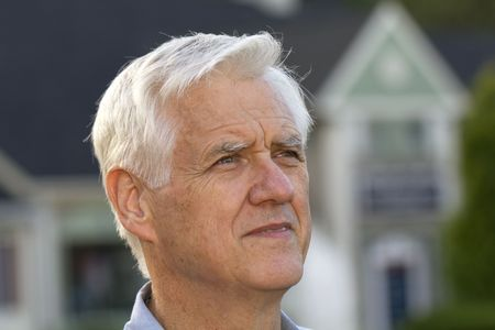 Portrait shot of senior man with defocused home outlines behind him reflect the universal effect of the recessions housing conditions