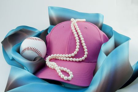 Pink baseball cap draped with elegant white pearls beside a white baseball are nestled in blue and brown ribbon against a white background to suggest a lifelong union of sports and feminine tastes