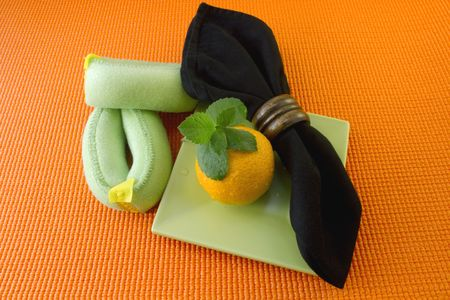Green wrist weights, an orange, mint leaves, and a black napkin agains an orange yoga mate reflect importnat points in a healthy lifestyle Stock Photo - 7634802