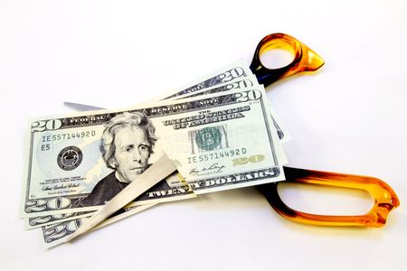 reduced value: American dollars cut by bright orange scissors on white background reflect consumers loss of spending power