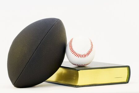Objects of athletics and scholarship isolated against a white background;  black football, white baseball, and gold edged text combine as a scholar athlete still life against a white background;  Stock Photo