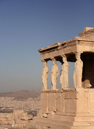 Porch and female statue columns of the Erechteion at Acropolis with city and sky to the left and back