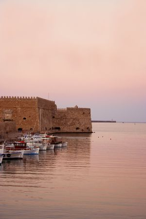 Sunset spills its colors onto waters of Crete's Chania Harbor near the Venetian Fortress and docked boats