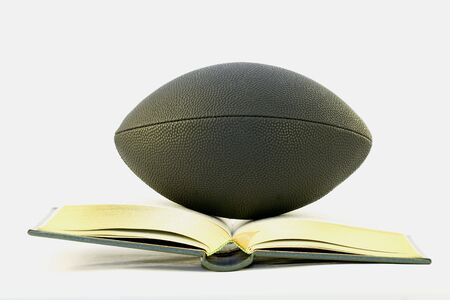 Black football balances on open, gold edged textbook against white background to signify the dual pressures of sports and studies;  Stock Photo
