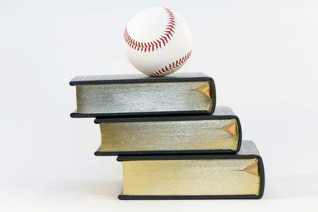 A baseball balances atop three books isolated against white background