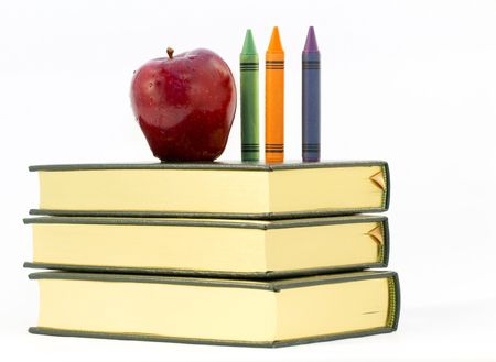 Red apple and three crayons sit on three textbooks Stock Photo - 7711053