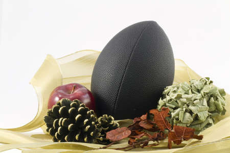 A black foot nestled in gold ribbon combines with autumn objects to depect sports autumn harvest against a white background
