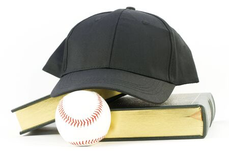Books, black baseball cap, and baseball rest together against a white background in still life of scholar and athlete objects