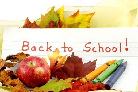 first day: Back to School written on primary school paper surrounded by autumn leaves, red apple, pine cones, and addition of gold ribbon to suggest the gift of learnings new opportunities found in the start of a new school year Stock Photo