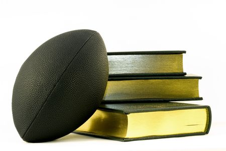 Black football leans against three, gold edged books, unifying symbols of sports, academics, and learning achievement