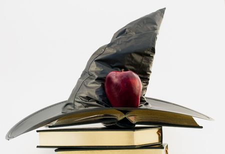 Witchs black hat and red apple atop open gilt edged, leather cover books against white background