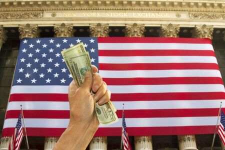 bidding: Fist filled with money raised before the American flag draped over the columns of the New York Stock Exchange