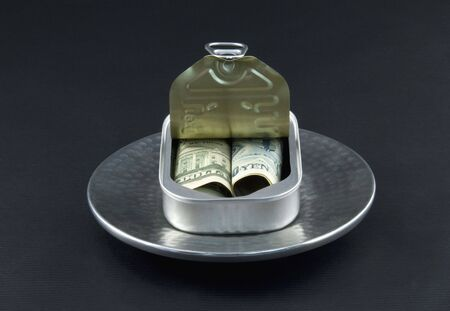diversification: Dollar and yen currency are rolled together into an open sardine can in a reflection of a new, basic diversification of investments  Stock Photo