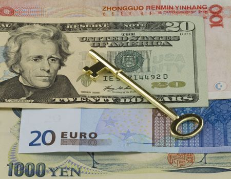 Golden key placed on multiple currencies,Dollars,  Euro, Yen, and RMB for worldwide business representation and empowerment