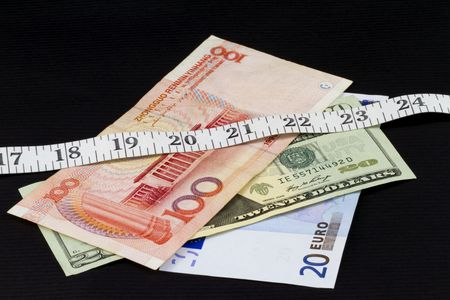 diversify: Modern currency beneath a measuring tape reflect the need to monitor closely the global, 21st century portfolio; currency of dollar, RMB, and euro on a black background;
