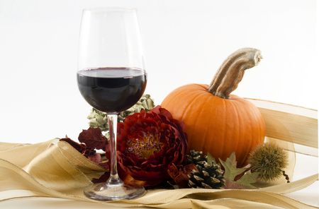 A glass of red wine with red blossom,seasonal  orange pumpkin and chestnut burr, pine cone and dry leaves offer an elegant toast and celebration of autumn