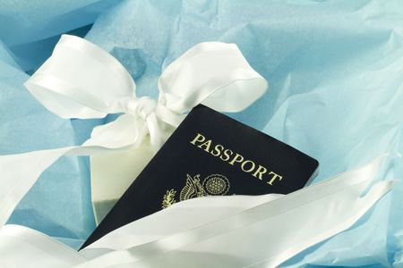 A passport nestles in blue tissue paper accented by a white ribbon to reflect the elegant choice of travel as an enabling and rewarding gift for any occasion;