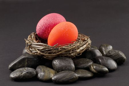 Crackled red and fluorescent orange nest eggs in a twig nest on rocks signal alarm and danger in investment environment and financial portfolio; danger colors of nest eggs signal that its time for fresh evaluation and direction; how are your nest eggs do photo