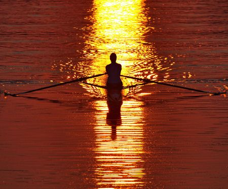 Lone crew rower strokes strongly in a shaft of early morning, red dawn sunlight on Lake Carnegie, Princeton, New Jersey Stock Photo