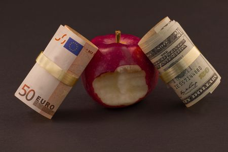 biten: Two currencies, euro and dollar, lean against a red apple with a bite taken out of it, representative of economic struggles as well as personal financial issues within those connected economies