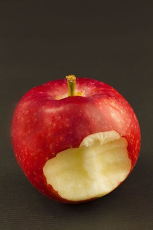 Red apple with firm, metaphoric bite taken from its flesh