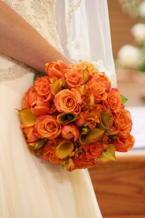 Bridal bouqet of orange roses and glimpse of an ivory wedding gown