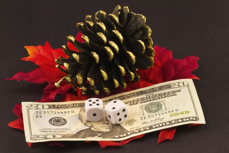 Dice on currency placed on red leaves next to a gold tipped pine cone reflect the financial bet investors make at years end when they balance their portfolios;