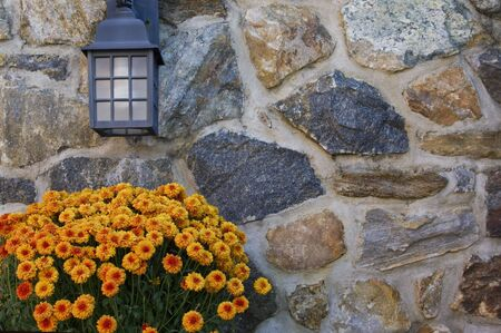 Orange autumn flowers beneath a garden light on a rough hewn stone wall