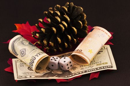 Winter and autumn images of pine cone and red leaves integrate with dice placed on American currency and next to currency bills of yen and euro.  This year continues to be mired in the risk created by the  precarious nature of world wide economies.   Stock Photo