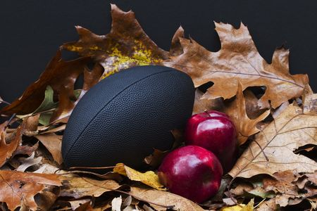 ripeness: Colorful autumn leaves depict the autumn season with two of its highlights: the game of football and the crisp ripeness of red apples; Stock Photo