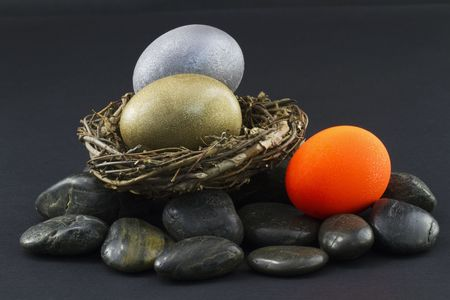 Three nest eggs with silver and gold doing well in nest and third, red nest egg on the rocks and out of the nest signifying a sector of the investment portfolio in need of attention Reklamní fotografie