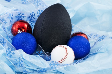 fixate: Festive holiday ribbon, Christmas ornaments, and a football and baseball on blue tissue paper; holiday and sports items combine for a festive holiday sports mood;