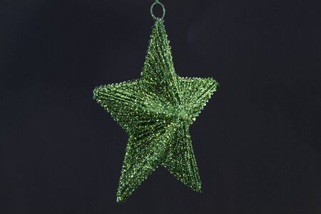 Elegant, single emerald green star ornament against black background with copy space Stock Photo
