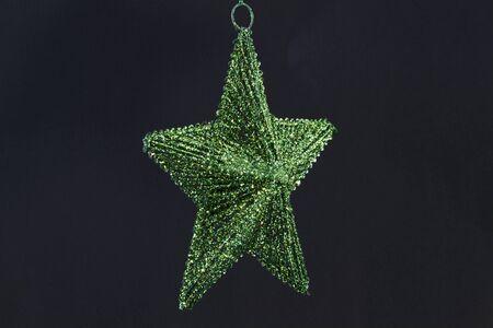 Elegant, single emerald green star ornament against black background with copy space Reklamní fotografie