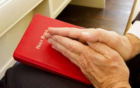 reverence: Mans hands held in prayer and placed on red Bible