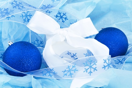 evocative: Small, white gift is an evocative mystery nestled in blue tissue, wrapped with a white satin ribbon, and with blue, glistening holiday ornaments at its sides Stock Photo