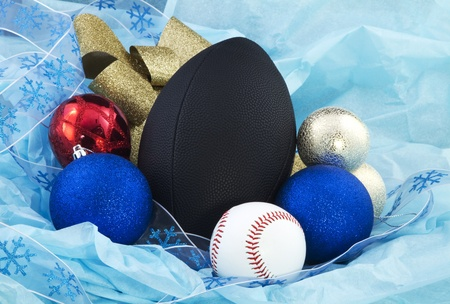 Baseball and football are surrounded by red, yellow, and gold Christmas balls and gold ribbon; 写真素材