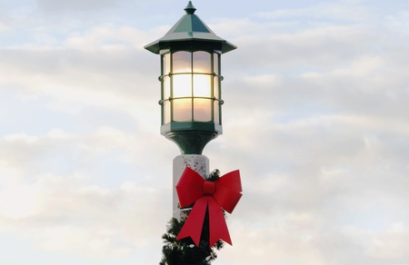 boughs: Street lamp decorated with pine boughs and red ribbon is lit against a soft blue and white cloud filled sunrise