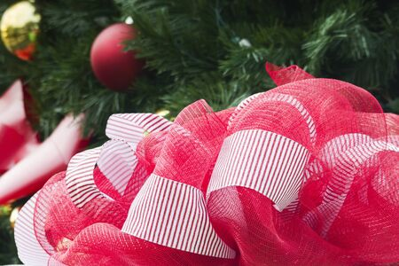 Selective focus and perspective reflects how a gift can fill a childs eyes with wonder; special gift highlights foreground in right corner; holiday view of red and white striped ribbon in foreground with unfocused tree and ornaments in background; Фото со стока
