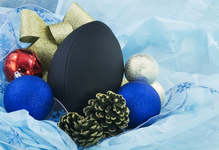 fixate: Football nestled with blue tissue paper, pine cones, and ornaments accents the holidays with an athletic flavor Stock Photo