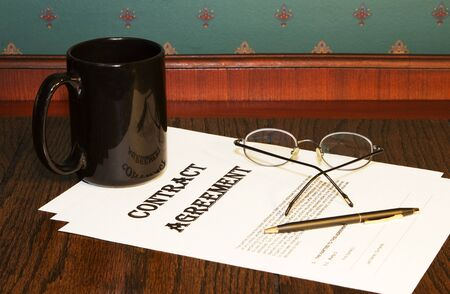 Contract agreement papers are in the decision process as shown by black coffee cup, reading glasses, and pen