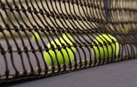 Multiple tennis balls roll against tennis nets base Imagens