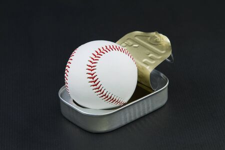 passions: Surprising image of opened sardine can releasing a baseball reflects sports passions and obsessions  Stock Photo