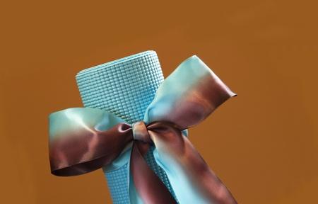 青いヨガマット角度に配置およびコピー スペースを提供する日焼けの壁の青および tan のサテンリボンをあしらった贈り物のような縛ら