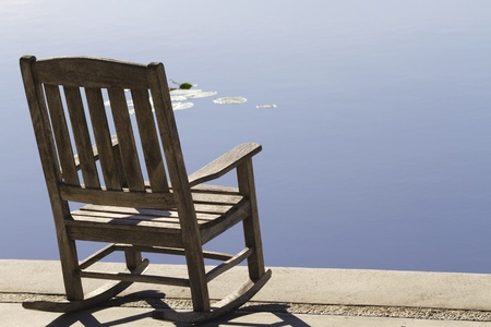 Wooden rocking chair sits by still water of urban lake creating an intense temptation to take a healthy, relaxing break