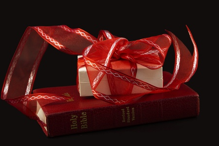 Red Bible with white gift wrapped in red  ribbon on simple, black background represents a cherished event photo